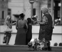 """Не жизнь, цветочки... / Вечер. Самый центр Москвы. Веселится и ликует весь народ, вышедший себя показать да на других поглазеть. У перехода стоит эта женщина, в попытке продать букетик. То опустит глаза с грустью, то встряхнет цветочки, то другой букетик достанет - """"Авось кому то люб покажется?""""... И снова поднимает глаза и теплая улыбка появляется на ее лице. Пробегаю мимо несколько метров, останавливаюсь. Делаю несколько кадров и до того щемяще становится, что не выдерживаю, возвращаюсь, даю какую то денежку. Столько благодарности в глазах. Прошу один портрет на память. Она смеется: """"Да, что ты, девонька, я ж некрасивая..."""" ...Вот такая жизнь... Вернее - не жизнь, а так.. цветочки сплошные..."""
