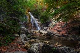 Водопад Джур-Джур / Одним из самых известных и старинных источников в Крыму, является водопад Джур-Джур. Древние греки называли Джур-Джур - «Кремасто-Неро», что в переводе на русский язык означает «висящая вода». Это название по праву оправдывается потому, что водопад не шумит и не грохочет, а его вода, плавно скользя вниз, лишь журчит, и в пыли мельчайших капелек воды висит радуга. Джур-Джур не пересыхает даже в самое жаркое лето. Этот водопад необычайно красивый и сильный. Река Улу – Узель падает по трехкаскадному порогу с 15 метровой высоты. Температура воды в водопаде – 7°С. Ширина водопада около 5 метров, вода мощным потоком несется вниз, в большой и глубокий котлован, и дальше течет вниз по реке. Под легкое журчание падающей вниз воды, можно наблюдать необычайное зрелище – на фоне возвышающихся гор, пенные струи водопада светятся в лучах солнца.