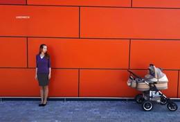 Мама и малыш в коляске / на фоне оранжевого фасада
