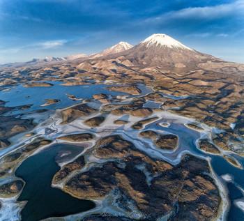 Близнецы / Вертикальная дронопанорама высокогорного озера на границе Боливии и Чили. На заднем плане знаменитые вулканы-близнецы Померапе и Паринакота (6300-6400 м) Национальный парк Лаука, Чили.