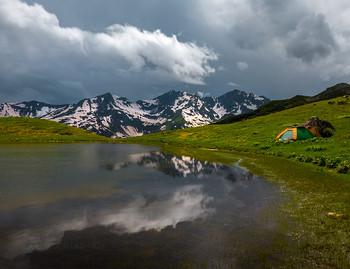 Палатка на берегу горного озера / Люблю путешествовать, особенно в горы с палаткой. Тем более интересные места для съёмки часто находятся далеко от дороги (иногда полдня ходу). И больше всего, я наслаждаюсь живя в палатке, вдалеке от туристических маршрутов, в полном покое, гармонии с природой. Никакие фото и слова не передадут это ощущение полного счастья. Когда днём занимаюсь своими делами (или отдыхаю после фотосъёмки, или читаю книгу, или обедаю) и при этом вокруг величественная красота гор, отражающее в озере бездонное небо с белоснежными кучевыми облаками, весенние запахи альпийских лугов после дождя и тишина! Ко всему этому не привыкнуть, всё кажется – «не может быть». Бытовые моменты похода, только подчёркивает это ощущение – будто нахожусь в приключенческом фильме. Это важный момент для моего творчества, влияющий на моё видение мира, понимание Природы.  Приглашаю насладиться путешествием и романтикой походной жизни в горах в фототуре «Сказочная Абхазия». Подробности здесь: https://www.facebook.com/groups/1755505914709044/(фейсбук) и https://vk.com/topic-69994899_38364547 (контакт).
