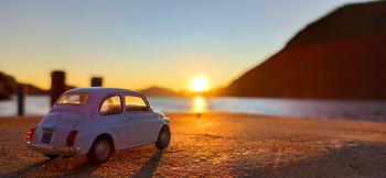 / La luce del tramonto di Montisola illumina il modellino della Fiat 500 in uno dei luoghi più famosi del lago