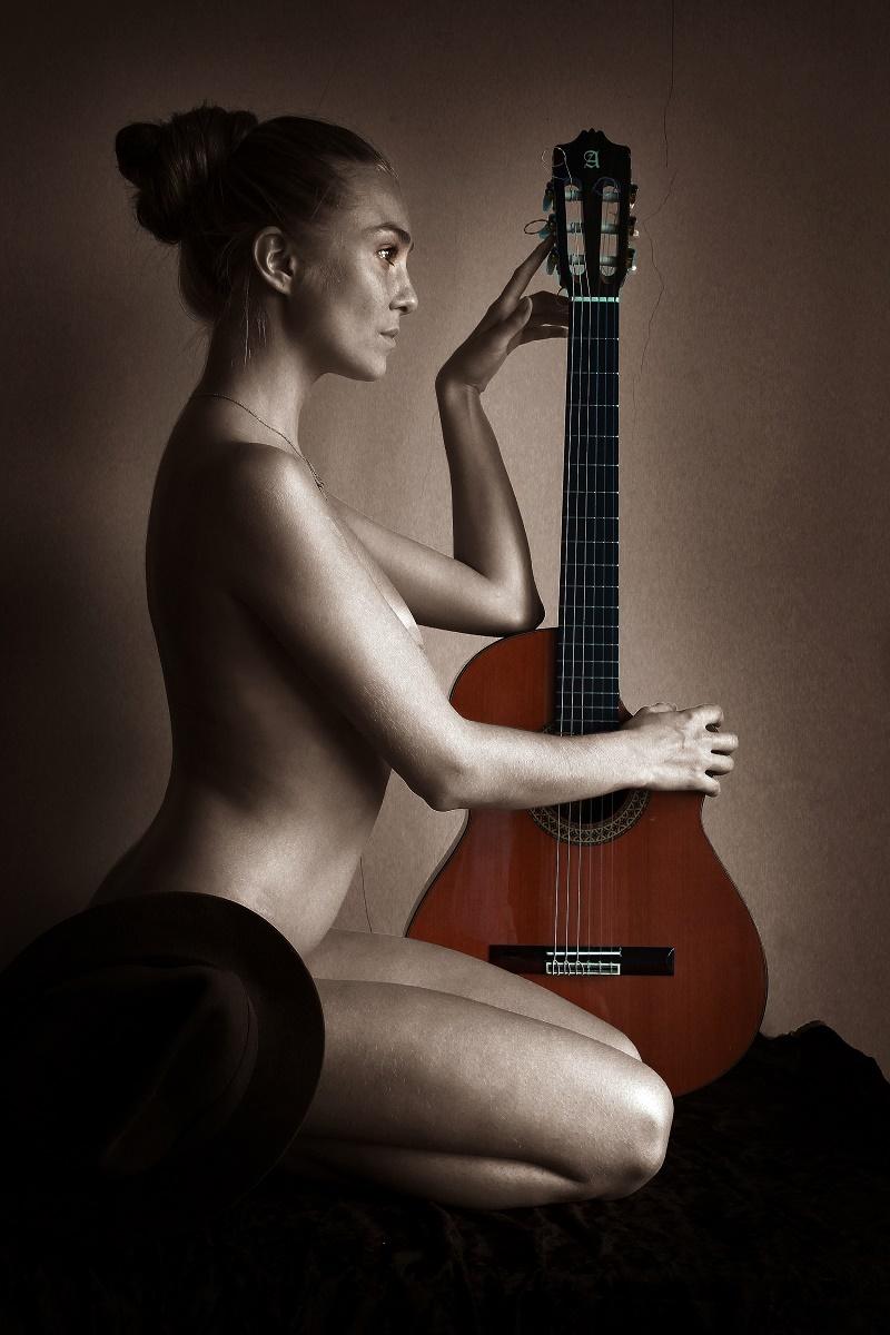 Naked blonde woman playing guitar